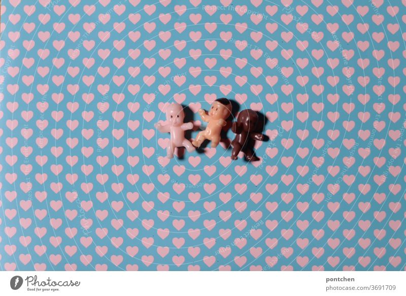 Three little baby dolls with different skin colours lie on a background with hearts. Love, tolerance, humanity, diversity Babies Skin color PoC People of color