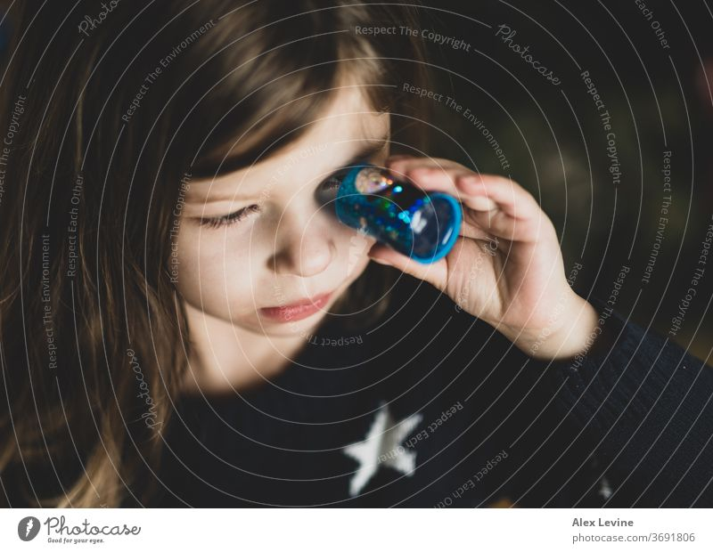 Child looking through a toy kaleidoscope child girl playing young playful science learning