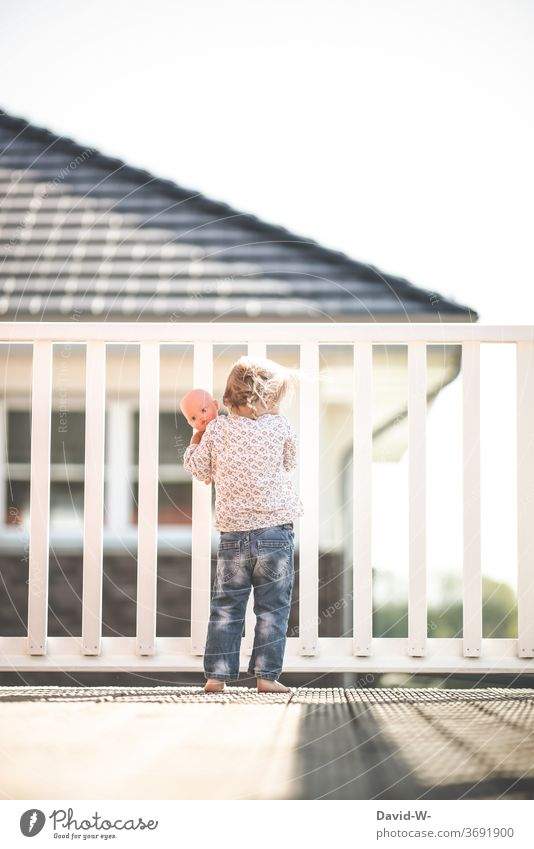 Girl with doll stands alone on the balcony and looks down from above Balcony girl peep out Grating Fence penned by oneself Doll Playing Observe Lonely being out