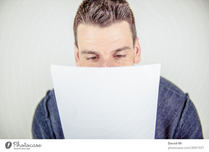 young man reads a piece of paper Piece of paper message Reading Young man Man adult read up Mail Letter (Mail) Message Paper Communicate Information Human being