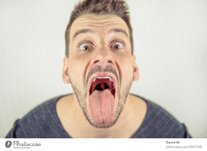 Man looks crazy into the camera with open mouth Mouth wide open Tongue Crazy Profile Face loopy portrait mouth opened Open lick show tongue