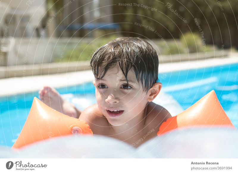 toddler with muffs and float on a mat in a swimming pool above ground pool ahead backyard boy calm caucasian child childhood floatie goggles inflatable kid