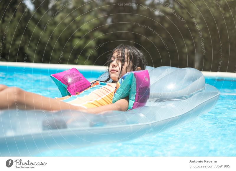 relaxed little girl with muffs on inflatable mat above ground pool ahead backyard calm caucasian child childhood float floatie goggles kid leisure looking male
