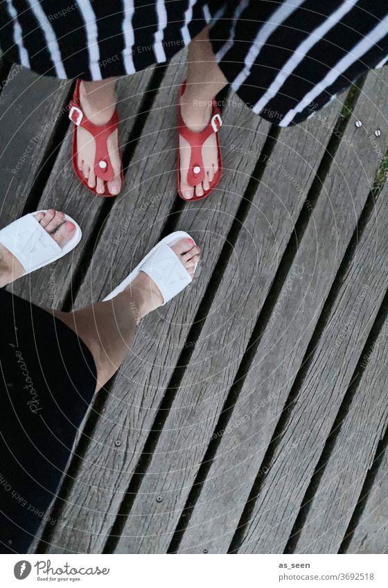Feet on the bar from above foot Footwear bathing shoes Sandals Legs wood wooden walkway Woman 2 High heels feminine Exterior shot Striped Pants Red White Gray