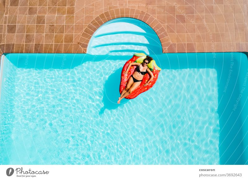 Woman floating on an ait mattress in a pool air beautiful bikini blue body cheerful copy copyspace drone enjoy enjoyment fashion female girl happiness holiday