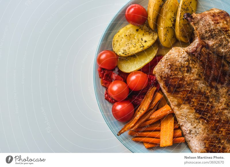 Grilled meat with vegetables. Tomato, carrot and potatoes. Healthy food. A flat lay shot of fried meat, potatoes, carrots and tomatoes on a plate carnivorous