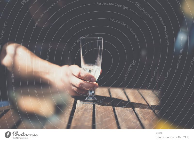 Alcoholism. One hand holds a nearly empty champagne glass on the table Champagne glass Alcoholic drinks To hold on Glass alcoholism Alcohol problem Addiction