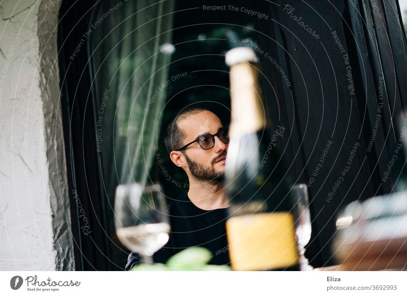 A man having a day drink with a bottle of Prosecco and glasses to a table. day drinking Alcoholic drinks Sparkling wine Garden Champagne glass Day Man Glass