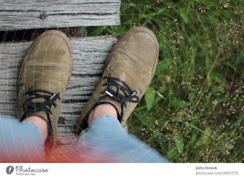 Shoes standing on wooden bridge photographed from a bird's eye view Footwear ecologic Sustainability Leather Cork Grass green Nature boards Screw Jeans