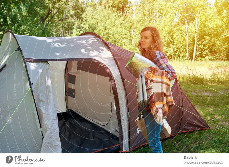 Woman setting up camping tent at the forest outdoor tourist hiking woman trees trip hike family adventure background discovery explorer hobby journey luggage