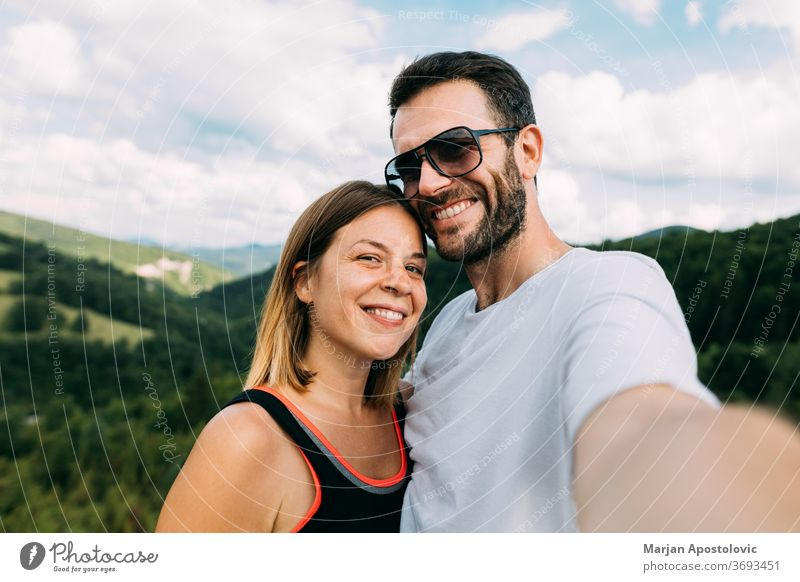 Young couple taking a selfie in the mountains adult adventure beautiful camera caucasian faces female freedom friends happy hike hiking journey landscape