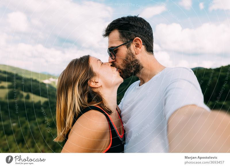 Young couple taking a selfie while kissing in the mountains adult adults adventure affectionate beautiful boyfriend camera casual caucasian cheerful emotional