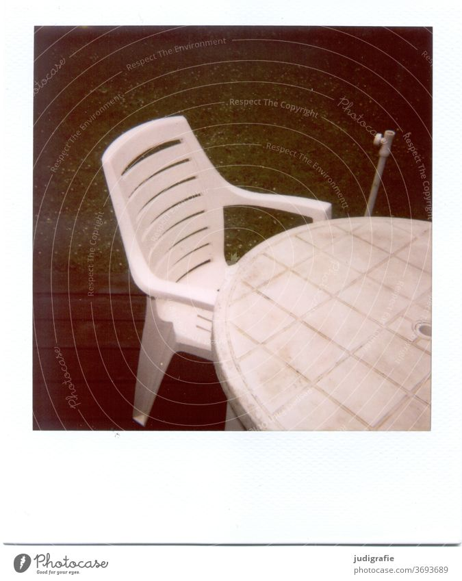 White garden chair with table on Polaroid Furniture Chair Garden chair Plastic chair Table Outdoor furniture Deserted Seating Exterior shot Colour photo Terrace