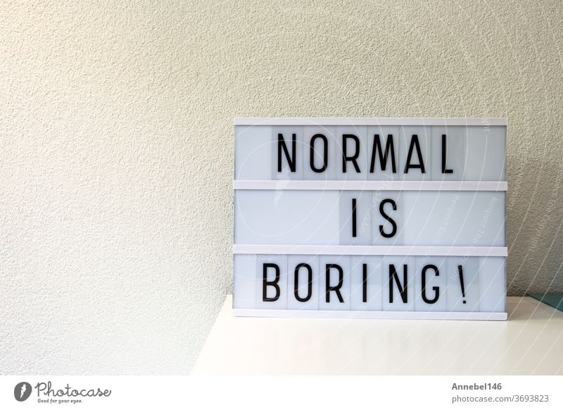 Normal is boring written in Light box home decoration, motivational sign retro home, space for text normal phrase white word concept background quote alphabet