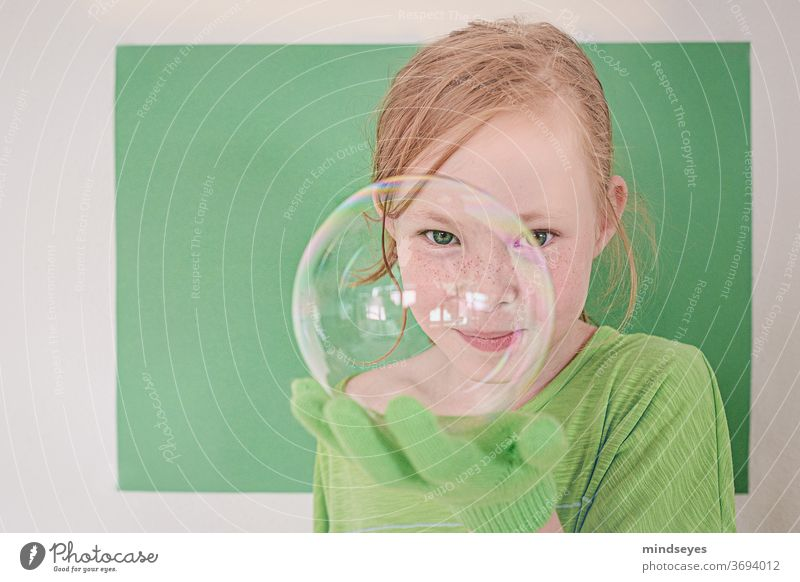 Girl in green looks cheekily through a soap bubble soap bubbles Soap bubble magic Gloves Playing fun Infancy Joy Funny Brash Freckles Child Colour photo