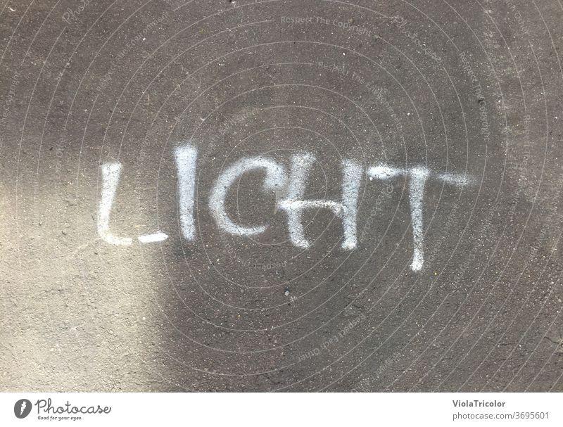 Light: sprayed lettering on asphalt Asphalt Street Sprayed White Gray Ground floor out daylight Shaft of light Handwriting Typography typo Word Bright spot