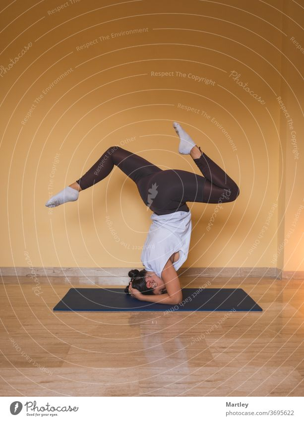 anonymous woman starting supported headstand pose. Side view of slim female doing yoga in cozy living room during daytime at home. girl meditation body indoors