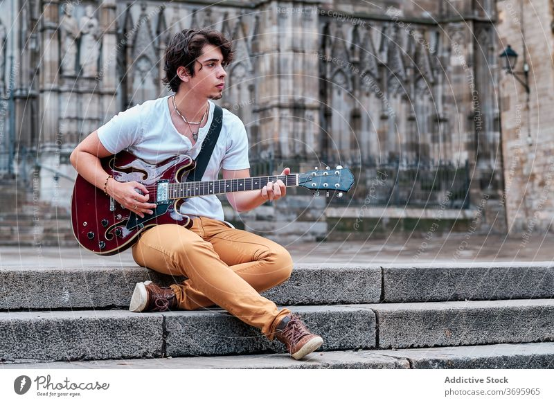Young man playing guitar on street city entertain music musician guitarist talent male stone calm sit step stair instrument song hobby relax guy sound melody