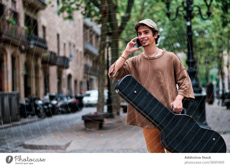Male musician talking on smartphone in city guitar man speak using guitarist talent male cellphone street gadget smile device communicate hipster mobile young