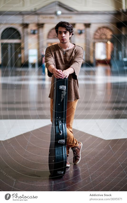 Young male guitarist in hall of building musician pensive city man case instrument solid spacious handsome style thoughtful professional inspiration modern