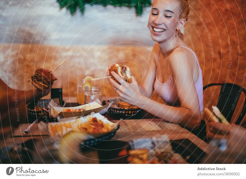 Happy young woman eating burger in cafe having fun fast food cheerful happy friend together hamburger laugh lifestyle friendship meeting communicate female