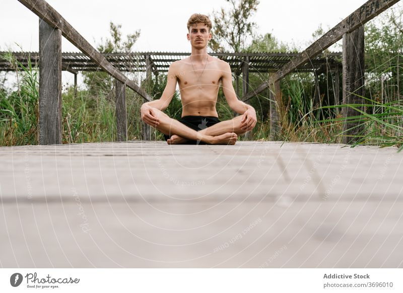 Man meditating in Lotus pose meditate lotus pose man yoga mindfulness stress relief nature tranquil harmony calm male wooden promenade healthy practice sit