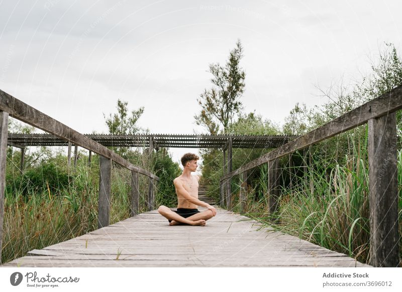 Shirtless man doing yoga on terrace padmasana practice flexible nature calm male pose harmony concentrate zen wooden healthy relax wellness balance stretch