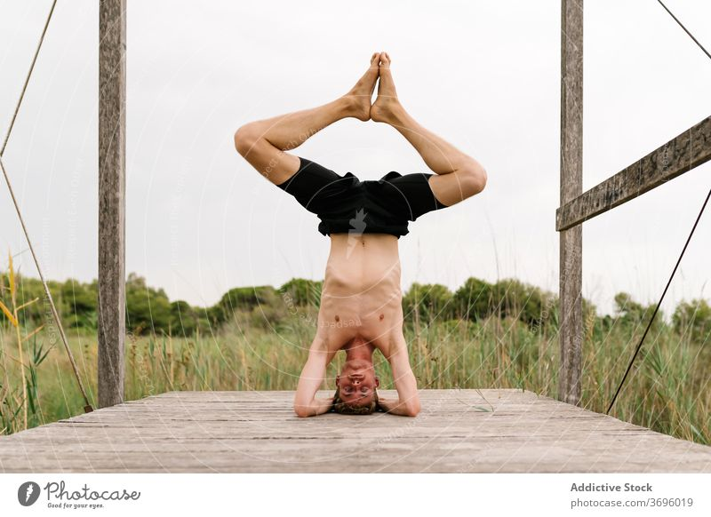 Tranquil man doing yoga in Supported Headstand posture headstand balance practice supported headstand pose asana salamba sirsasana tranquil male shirtless relax