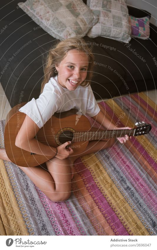 Girl sitting on the floor playing a guitar while is smiling and facing the camera vertical music artist classical learning musician practice room smile string