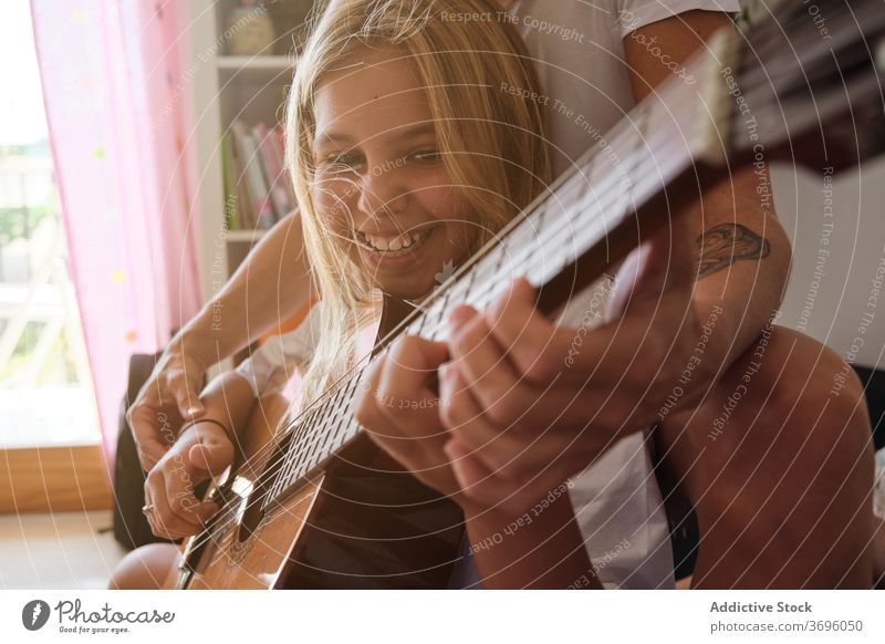 Smiling girl and a woman playing guitar in a house music teacher education learning student teaching lesson instrument musician performance pupil study class
