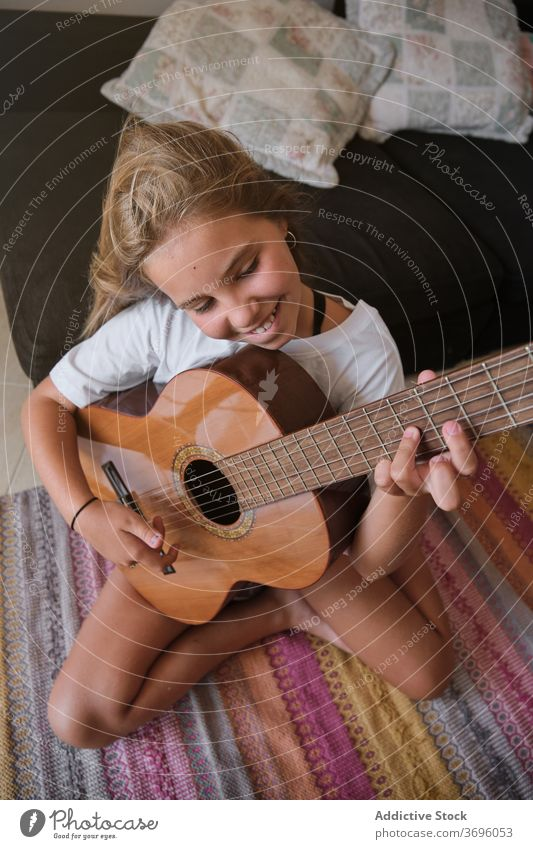 Girl sitting on the floor of a house playing a guitar with happy expression music artist classical learning musician practice room smile string instrument
