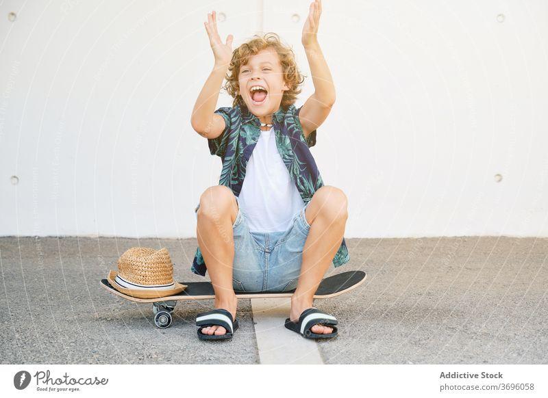 Child in summer clothes sitting on a skateboard gesturing joyfully dynamic extreme skill vitality skater skateboarder adolescence balance challenge children