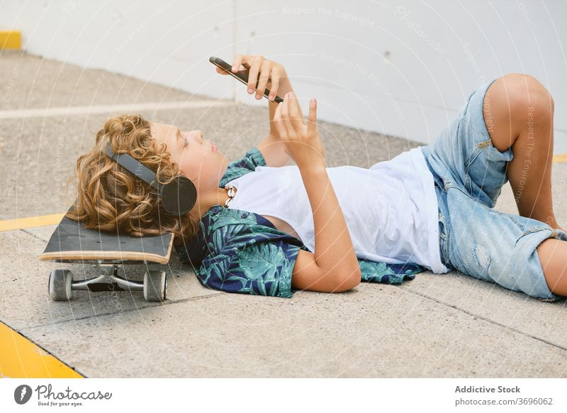 Boy lying on the floor with a skateboard listening to music and looking his mobile adolescence solitude singing trend generation teen weekend sound teenager