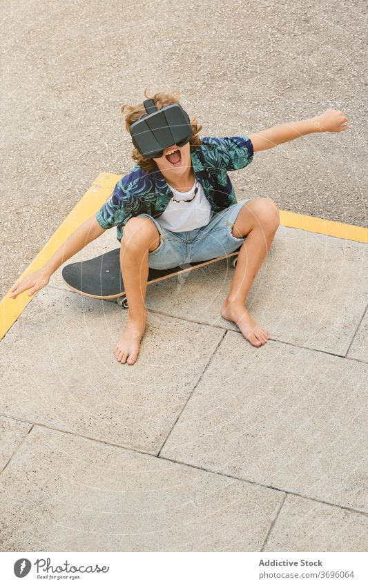 Boy sitting on a skateboard wearing virtual reality glasses and gesturing as he flies vertical reaction touching optical dimensional experience headset