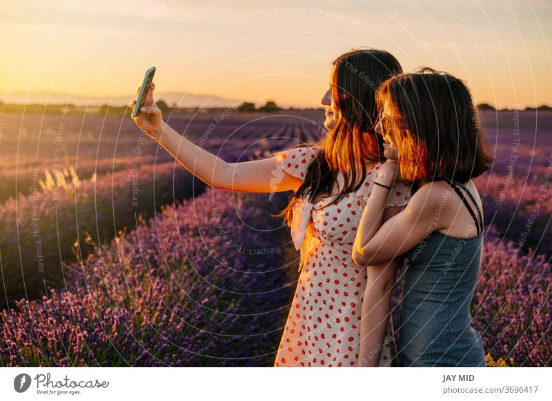 Two friends take photos with their mobile phone in a field of blooming lavenders woman´s two holiday make photos selfie summer vacation blossom enjoy fun play