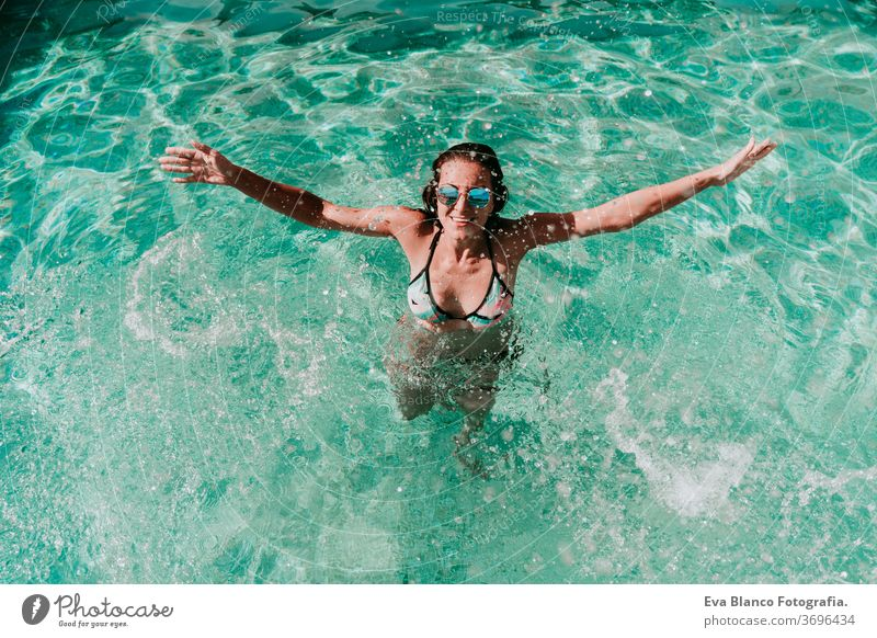 happy woman at the pool having fun splashing water. Summer and lifestyle one swimming pool sunglasses summer blue water hot playing laughter float party