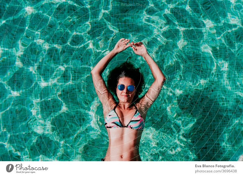 top view of happy young woman floating in a pool. summer and fun lifestyle underwater swimming bubbles caucasian dive clear health light action wet swimmer blue