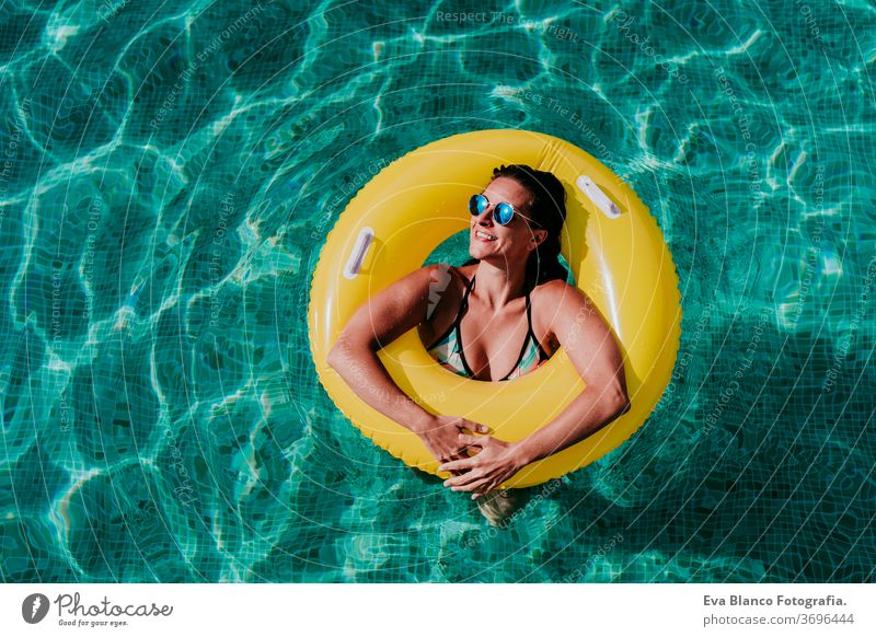 top view of happy young woman floating in a pool in a yellow donuts. summer and fun lifestyle inflatable swimming bubbles caucasian dive clear health light