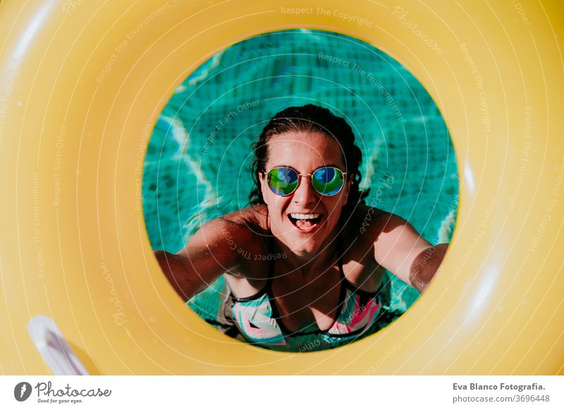top view of happy young woman in a pool holding a yellow donuts. summer and fun lifestyle inflatable swimming bubbles caucasian dive clear health light water