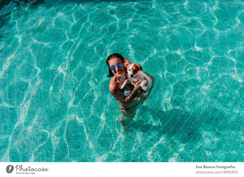 happy young woman and dog in a pool having fun. Summer time swimming pool blue water summer time love jack russell hat together togetherness kiss purebred