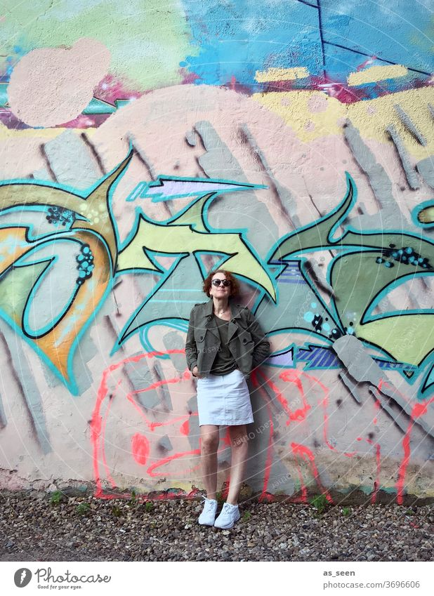 Woman with sunglasses in front of a wall with graffiti Graffiti sneakers Sunglasses lured Red-haired Exterior shot Day Human being Fashion green Khaki