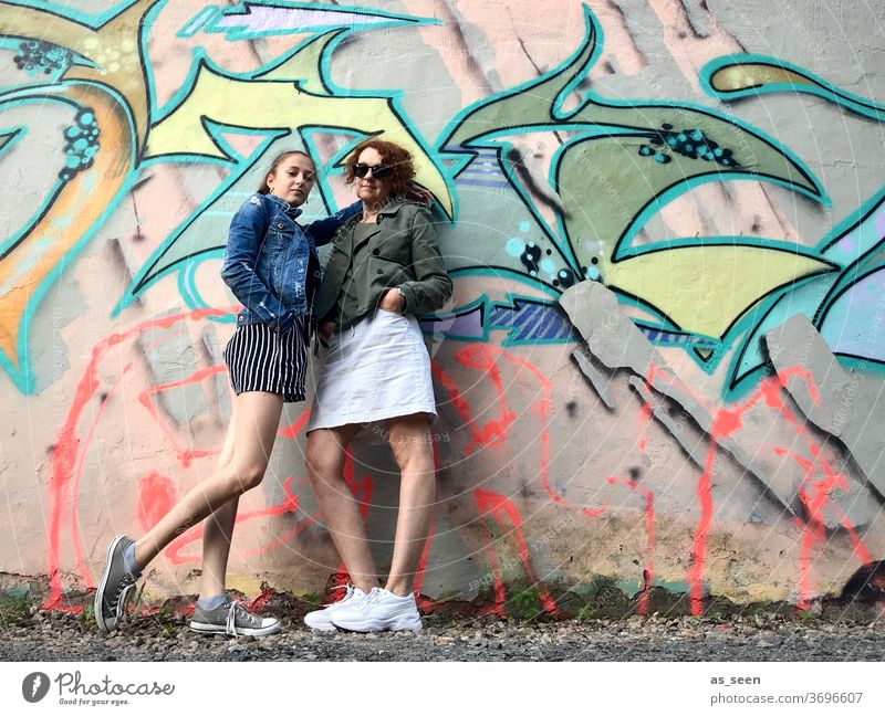 Two women in front of a wall with graffiti Graffiti sneakers Sunglasses lured Red-haired Exterior shot Day Human being Fashion green Khaki variegated Pattern