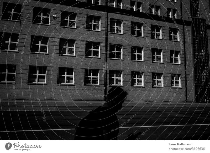 Shadow of a person in front of a house Exterior shot Light City people Modern Architecture Human being Wall (building) Town Lanes & trails Road traffic activity