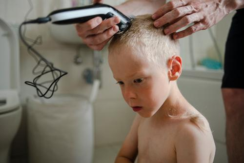 Father making haircut for son at home hairstyle child care machine bathroom family hand hairdresser man trimmer face young quarantine head caucasian male people