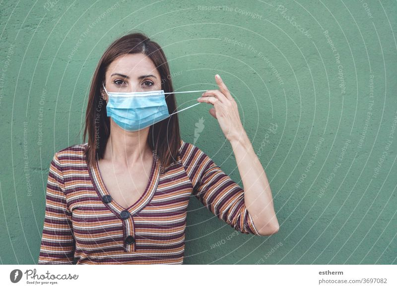 woman wearing medical mask holding a protective medical mask coronavirus young woman epidemic pandemic quarantine covid-19 symptom medicine health