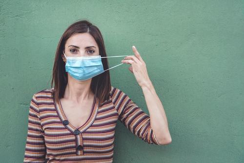 woman wearing medical mask holding a protective medical mask coronavirus young woman epidemic pandemic quarantine covid-19 symptom medicine health