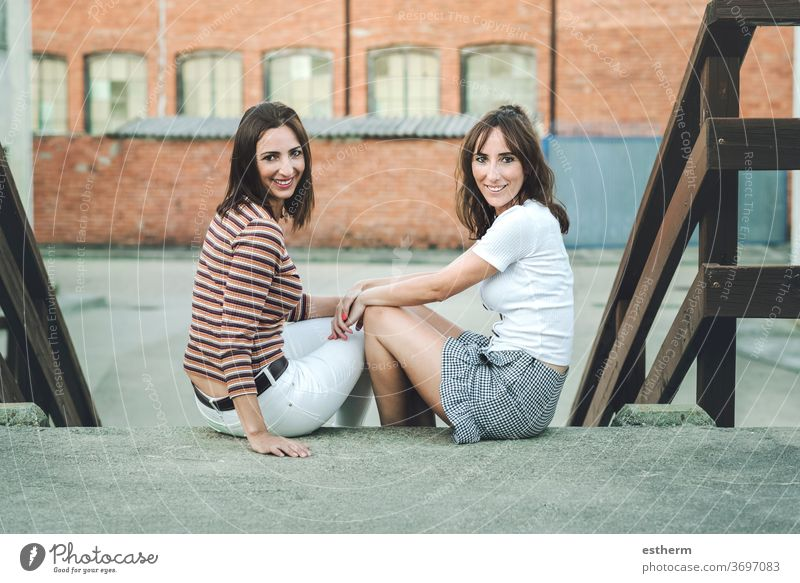 young women friends sitting on the street two people standing sister urban funny holiday travel outdoors beauty fashion life relationship portrait expression