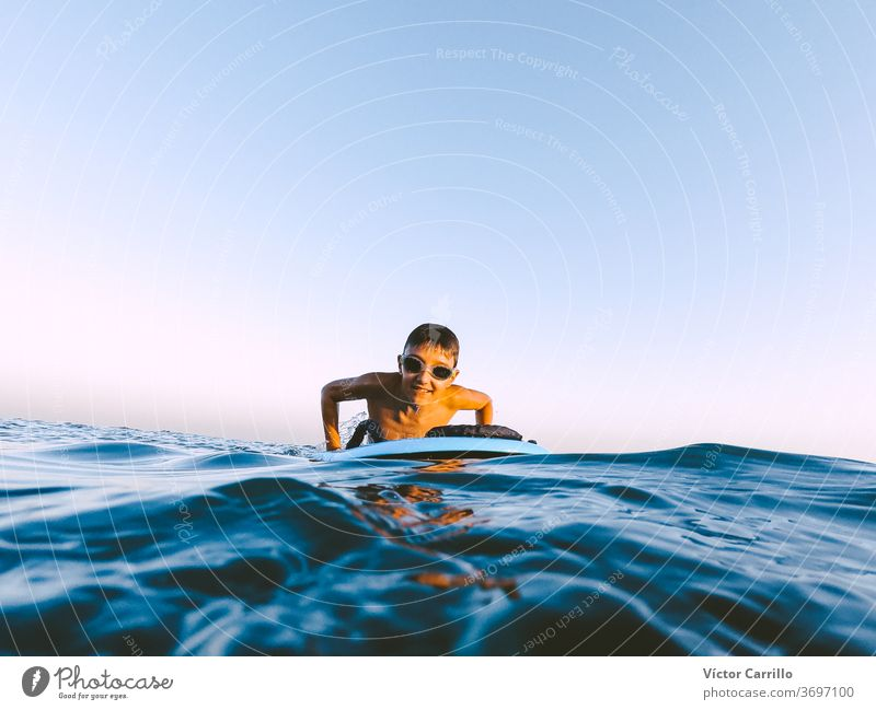 A young boy learning in body board outdoors in the shoreline in a sunny day of summer bodyboarder child holiday vacation leisure lifestyle surfboard surf-riding