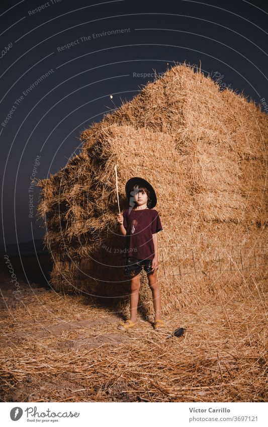A young boy with a hat playing in the fields of the country side in summer in a straw bale background farmer boy crouching plant autumn kid cute fall plantation