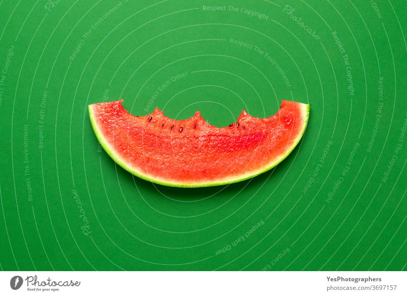 Slice of watermelon isolated on a green background. Bitten slice of watermelon top view. above view bitten colored colorful cut cut out detox diet eat eaten